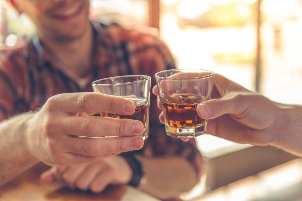 Cropped image of two men clanging glasses of alcoholic beverage together while sitting at bar counter in a modern urban cafe